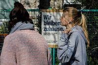 """Two woman walk by a restaurant with a sign up which reads """"We Stay at Home"""" in Berlin's Kreuzberg district on March 27, 2020 during the new coronavirus COVID-19 pandemic. (Photo by David GANNON / AFP)"""