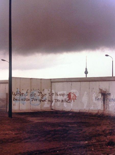 """Berlin, April 1980: Blick über die Mauer vom Westteil der Stadt in Richtung Alexanderplatz mit dem Fernsehturm im damaligen Ost-Berlin, der """"Hauptstadt der DDR""""."""