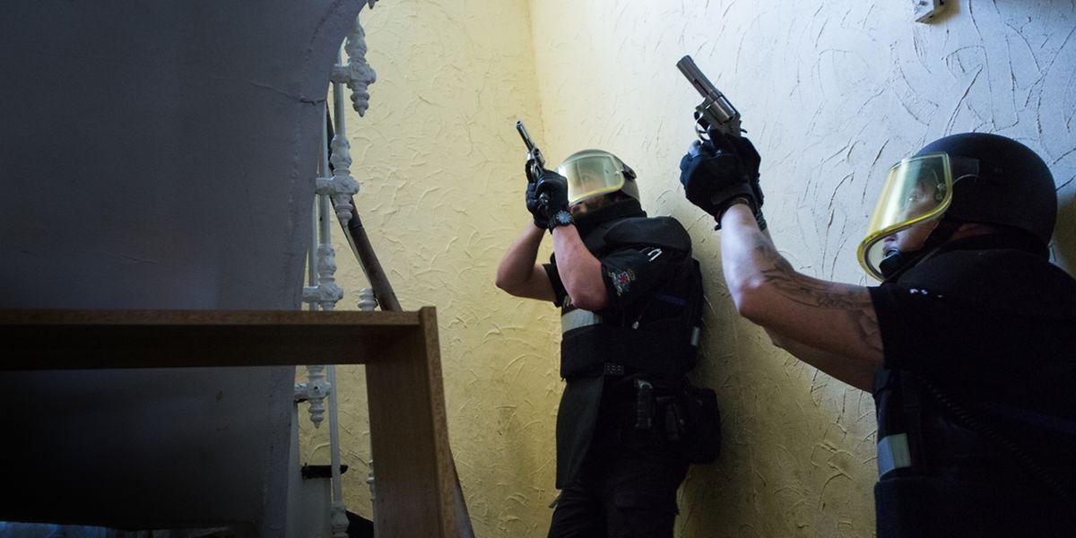 Vorsichtig und mit gezückter Waffe bewegen diese Polizisten sich durch das Haus, in dem sich der Verdächtige befindet.
