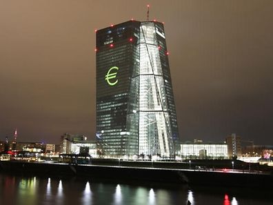 """The Euro-logo is projected onto the main building of the European Central Bank, ECB during a rehearsal of the """"Luminale"""" in Frankfurt/Main, Germany, on March 12, 2016. The light festival """"luminale"""" runs from March 13 to 18, 2016.  / AFP PHOTO / DANIEL ROLAND"""