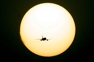 A plane flies in front of sun during sunset at New Delhi airport April 10, 2005.   REUTERS/Kamal Kishore