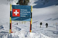 "Skiers hit the slopes past a banner showing Swiss border above the ski resort of Zermatt in the Swiss Alps on November 28, 2020. - In non-EU Switzerland, which has been hard-hit by the second wave of Covid-19, the authorities, ski and tourism sectors have stood united behind the decision to keep the winter season going as EU countries debate a bloc-wide ban on ski holidays to curb coronavirus infections. ""In Switzerland, we can go skiing, with protection plans in place,"" Swiss Health Minister Alain Berset told reporters on November 26, 2020. (Photo by Fabrice COFFRINI / AFP)"