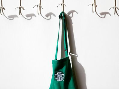A barrista's apron hangs on a peg in Starbucks