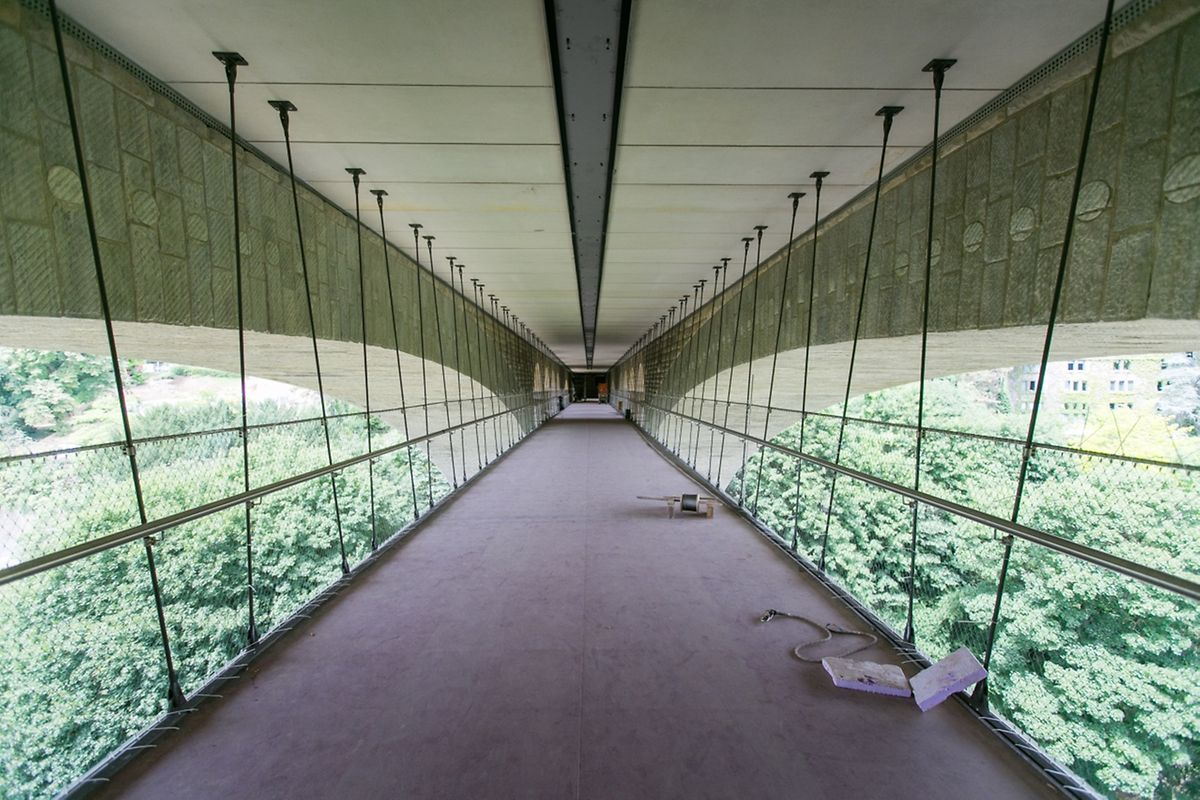 Die Konstruktion aus Leichtmetall ist auf einer Länge von 154 Meter über Drahtseile in der Fahrbahndecke des Pont Adolphe verankert.