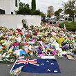19.03.2019, Neuseeland, Christchurch: Eine Fahne von Neuseeland und Blumen liegen vor der Al-Nur-Moschee, um den Opfern eines rassistisch motivierten Anschlags zu gedenken. Bei einem rassistisch motivierten Doppelanschlag auf zwei Moscheen tötete der mutmaßliche Täter am 15.03.2019 im neuseeländischen Christchurch mindestens 50 Menschen. Foto: Mick Tsikas/AAP/dpa +++ dpa-Bildfunk +++