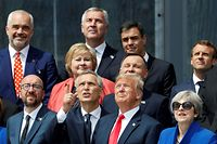 (Front row, LtoR) Belgium's Prime Minister Charles Michel, NATO Secretary General Jens Stoltenberg, US President Donald Trump, Britain's Prime Minister Theresa May and Estonia's Prime Minister Juri Ratas and other NATO leaders watch a helicopter flyover as they attend the opening ceremony of the NATO (North Atlantic Treaty Organization) summit, at the NATO headquarters in Brussels, on July 11, 2018.  / AFP PHOTO / GEOFFROY VAN DER HASSELT