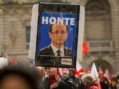 """A man holds a picture of French president Francois Hollande reading """"Shame"""" during a demonstration against the French government's proposed labour reforms"""
