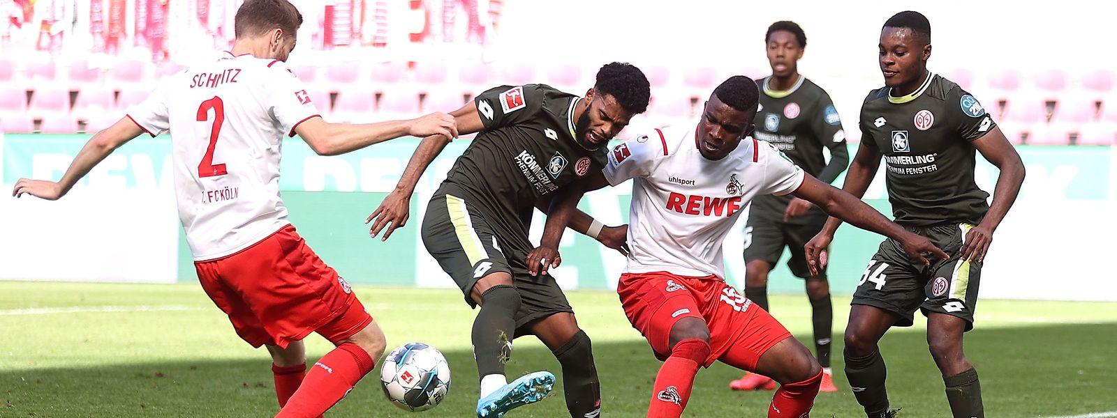Der Mainzer Jeremiah St. Juste verteidigt den Ball gegen die Kölner Benno Schmitz (l.) und Jhon Cordoba.