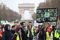 """Yellow Vests"" (Gilets Jaunes) protesters hold a sign reading ""end of the world end of the month same fight"" as they take part in an anti-government demonstration in front of the Arc de triomphe in Paris, on March 9, 2019. - ""Yellow Vests"" protesters take to the streets for the 17th consecutive Saturday with a rallying dedicated on March 9, 2019 to the women's rights. This movement in France originally started as a protest about planned fuel hikes but has morphed into a mass protest against President's policies and top-down style of governing. (Photo by KENZO TRIBOUILLARD / AFP)"