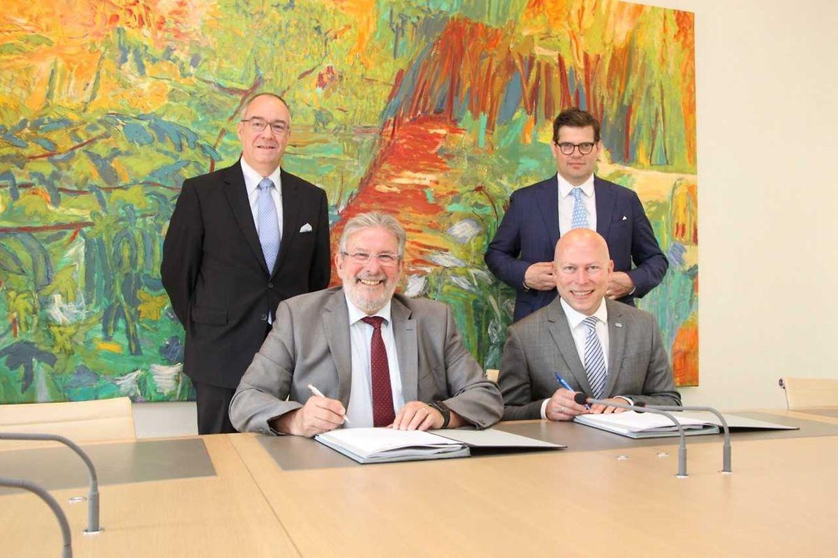 Mars di Bartolomeo und Stéphane Pallage unterzeichneten das Abkommen im Beisein von Claude Frieseisen (l) und Philippe Poirier.