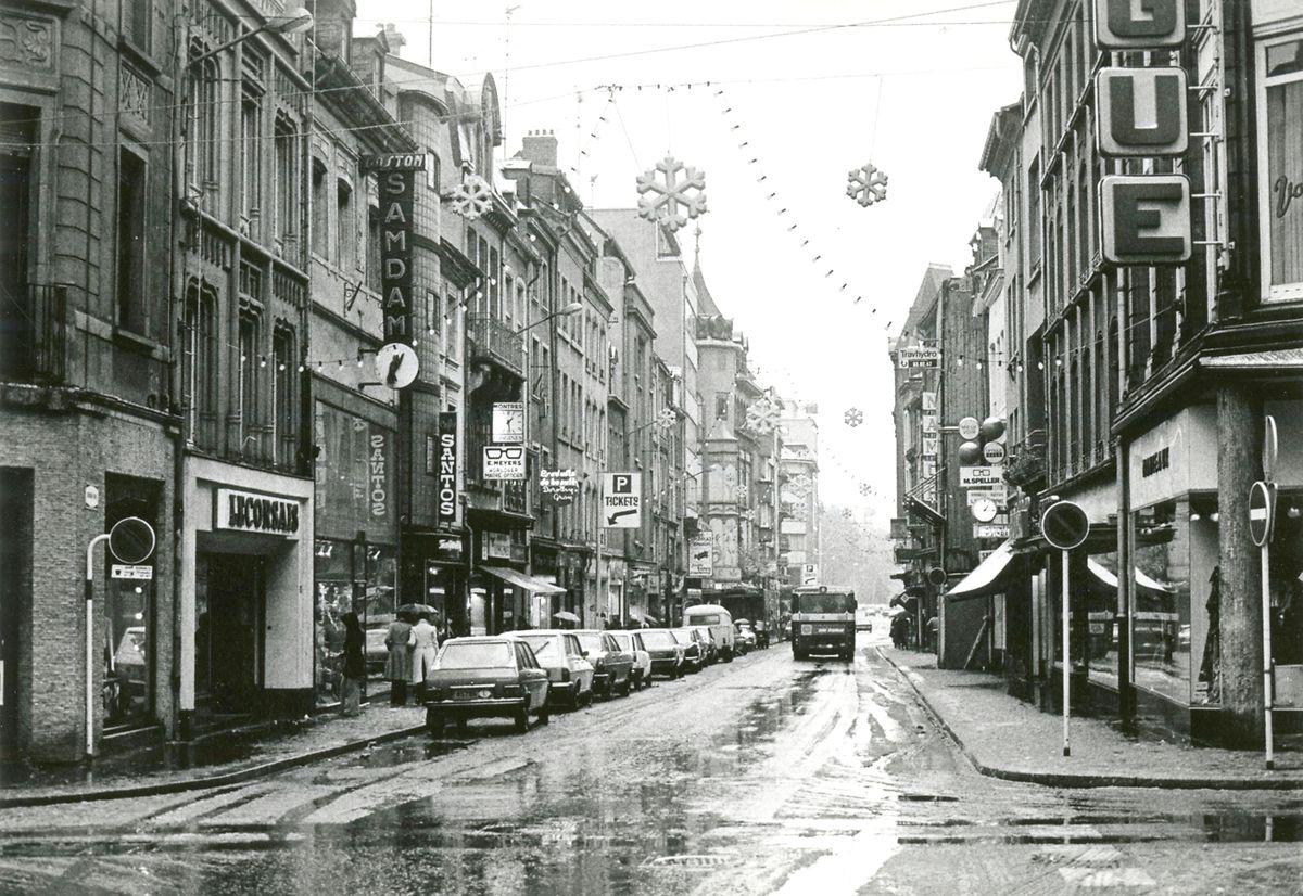 "Décembre 1976: la Grand-Rue est encore livrée au trafic des engins à moteur.   Durchgangsverkehr und Stellplätze: Die Groussgaass drei Jahre vor der Umgestaltung zur ""Zone piétonne"". Die Aufnahme stammt von Dezember 1976."