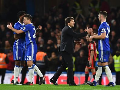 Chelsea's Italian head coach Antonio Conte (2R) shakes hands with Chelsea's English defender Gary Cahill (R) at the end of the English Premier League football match between Chelsea and Bournemouth at Stamford Bridge in London on December 26, 2016. / AFP PHOTO / Ben STANSALL / RESTRICTED TO EDITORIAL USE. No use with unauthorized audio, video, data, fixture lists, club/league logos or 'live' services. Online in-match use limited to 75 images, no video emulation. No use in betting, games or single club/league/player publications.  /