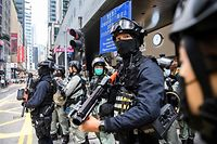 TOPSHOT - Riot police take part in a crowd dispersal operation in the Central district of Hong Kong on May 27, 2020, as the city's legislature debates over a law that bans insulting China's national anthem. - Hong Kong police cast a dragnet around the financial hub's legislature on Wednesday, firing pepper-ball rounds and arresting hundreds as they stamped down on protests against a bill banning insults to China's national anthem. (Photo by ANTHONY WALLACE / AFP)