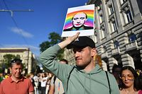 """A participant holds a placard showing Russian President Vladimir Putin, in front of the parliament building in Budapest on June 14, 2021, during a demonstration against the Hungarian government's draft bill seeking to ban the """"promotion"""" of homosexuality and sex changes, which will be discussed by Hungarian MPs tomorrow. - The Hungarian ruling party of right-wing Prime Minister Viktor Orban on June 10, 2021 introduced legislative amendments seeking to ban the """"promotion"""" of homosexuality and sex changes. The move was swiftly denounced by Amnesty International, Budapest Pride and three other rights groups who compared the Fidesz party proposals to a similar law in Russia which punished acts of homosexual """"propaganda"""" aimed at young people. If the Hungarian move becomes law it would effectively ban educational programmes and publicity of LGBT groups, according to the 11-page document seen by AFP. (Photo by GERGELY BESENYEI / AFP)"""