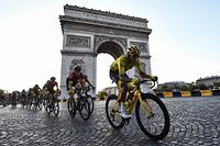 TOPSHOT - Colombia's Egan Bernal (R), wearing the overall leader's yellow jersey (C-R) and cyclists ride down the Champs Elysees avenue next to the Arc de Triomphe during the 21st and last stage of the 106th edition of the Tour de France cycling race between Rambouillet and Paris Champs-Elysees, in Paris, on July 28, 2019. (Photo by Anne-Christine POUJOULAT / AFP)