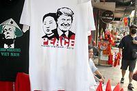 """21.02.2019, Vietnam, Hanoi: T-Shirts, auf denen die Porträts des US-Präsidenten Trump und des nordkoreanischen Machthabers Kim über dem Schriftzug """"Peace"""" zu sehen sind, hängen an einem Verkaufsstand. (zu dpa """"Kegelhut-Trump und «Peace» mit Kim:T-Shirts sind in Hanoi der Renner"""" Foto: Bac Pham/dpa +++ dpa-Bildfunk +++"""