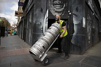 (FILES) In this file photo taken on April 09, 2021 Niall Coghlan delivers barrels of beer from Brixton Brewery to a bar in Brixton, south London on April 9, 2021 ahead of the easing of coronavirus restrictions to allow pub beer gardens in England to reopen on April 12. - Britain took another tentative step towards the resumption of normal life on April 12, as pubs and restaurants were allowed to partially reopen, in a major easing of coronavirus restrictions. Pubs and restaurants across England can now serve drinkers and diners outside, bringing some cheer to the beleaguered hospitality industry after repeated closures over the last year. (Photo by Tolga Akmen / AFP)