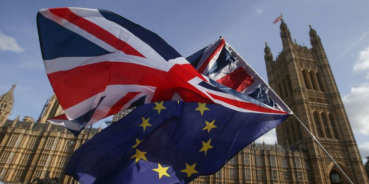 "Demonstrators fly a Union flag (top), and an EU flag outside of the Houses of Parliament in Westminster, central London on October 12, 2017. Britain and the EU are stuck in a ""disturbing"" deadlock over the Brexit divorce bill, although a breakthrough remains possible in the next two months, EU negotiator Michel Barnier said Thursday. The stalemate will stoke fears swirling in London and Brussels of a breakdown in talks that could see Britain leaving the European Union in March 2019 without an agreement to soften the blow. / AFP PHOTO / Daniel LEAL-OLIVAS"