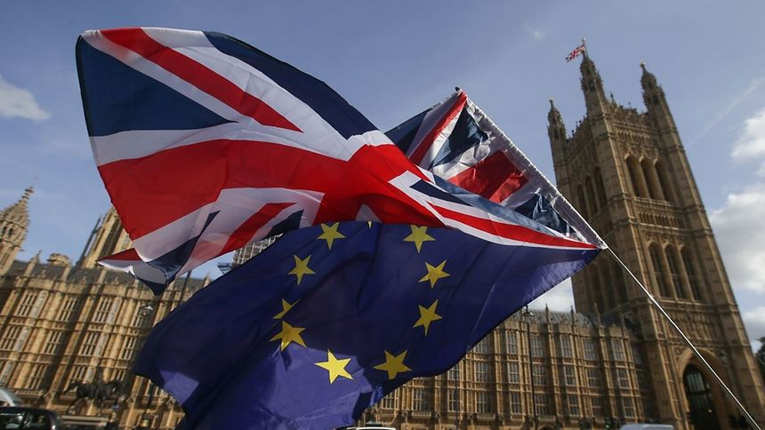 """Demonstrators fly a Union flag (top), and an EU flag outside of the Houses of Parliament in Westminster, central London on October 12, 2017. Britain and the EU are stuck in a """"disturbing"""" deadlock over the Brexit divorce bill, although a breakthrough remains possible in the next two months, EU negotiator Michel Barnier said Thursday. The stalemate will stoke fears swirling in London and Brussels of a breakdown in talks that could see Britain leaving the European Union in March 2019 without an agreement to soften the blow. / AFP PHOTO / Daniel LEAL-OLIVAS"""