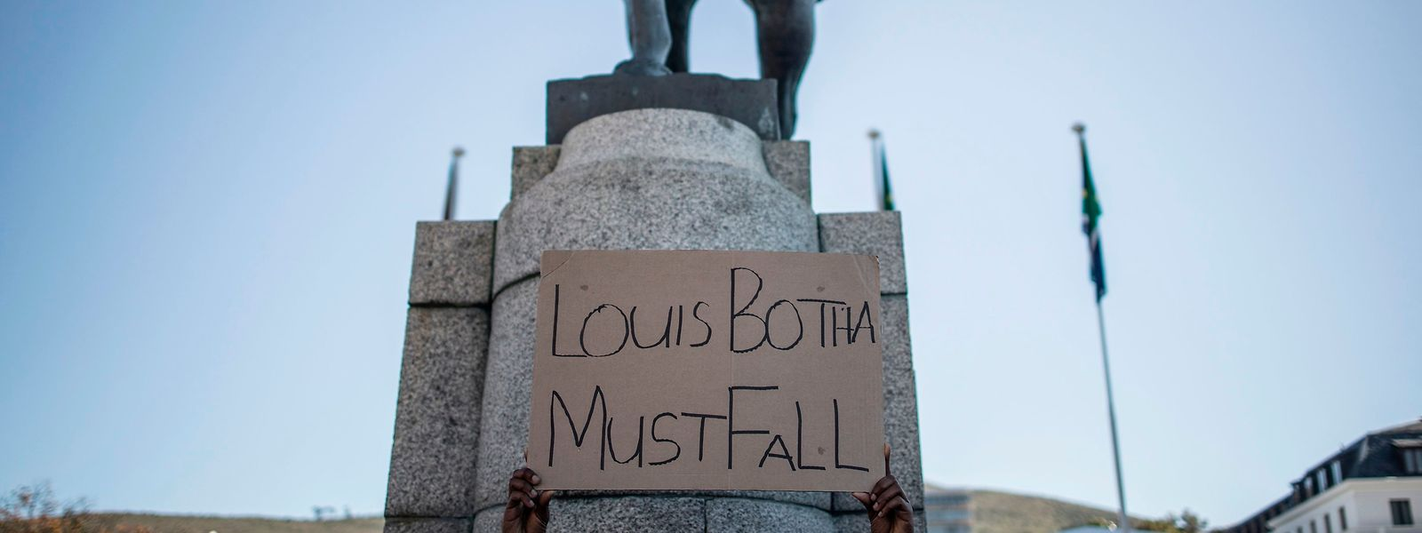 Rassismusdebatte in Südafrika: Ein Demonstrant hält ein Plakat in der Hand vor einem Denkmal von Louis Botha, dem ersten Premierminister der Union von Südafrika. Demonstranten fordern die Entfernung der Statue vor dem Parlament in Kapstadt.