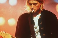 """An undated file photo shows """"Nirvana"""" lead singer and guitarist Kurt Cobain performing on stage. Cobain committed suicide at his home in Seattle on April 8, 1994.   Cobain, who raked in an estimated $50 million between October 2005 and October of this year, has edged Elvis Presley from the No. 1 spot on Forbes.com's list of """"Top-Earning Dead Celebrities.""""  (AP Photo)"""