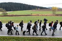 (FILES) This file photo taken on November 09, 2015 shows migrants walking on the road after crossing the Austrian-German border near the Bavarian village of Wegscheid, southern Germany.  As Germany struggles to cope with the arrival of more than one million refugees, the country's rural communities could hold the key to integrating the newcomers and even stand to benefit themselves in face of dwindling populations, experts say. / AFP / CHRISTOF STACHE