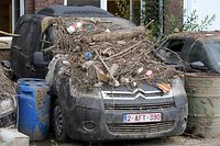 A picture taken on July 26, 2021 shows a car covered with rubble in the Belgian town of Trooz, a week after heavy rains and floods lashed western Europe. - In mid-July western Europe was hit by devastating floods after torrential rains that ravaged entire villages and left at least 209 people dead in Germany and Belgium, as well as dozens missing. Up to two months' worth of rainfall came down in two days in some parts of the region, waterlogging soil that was already near saturation. (Photo by Fran�ois WALSCHAERTS / AFP)