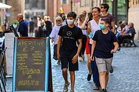 Teenagers wearing a face mask stroll past a restaurant across Rome's Jewish Quarter on September 15, 2020 during the COVID-19 infection, caused by the novel coronavirus. (Photo by Vincenzo PINTO / AFP)