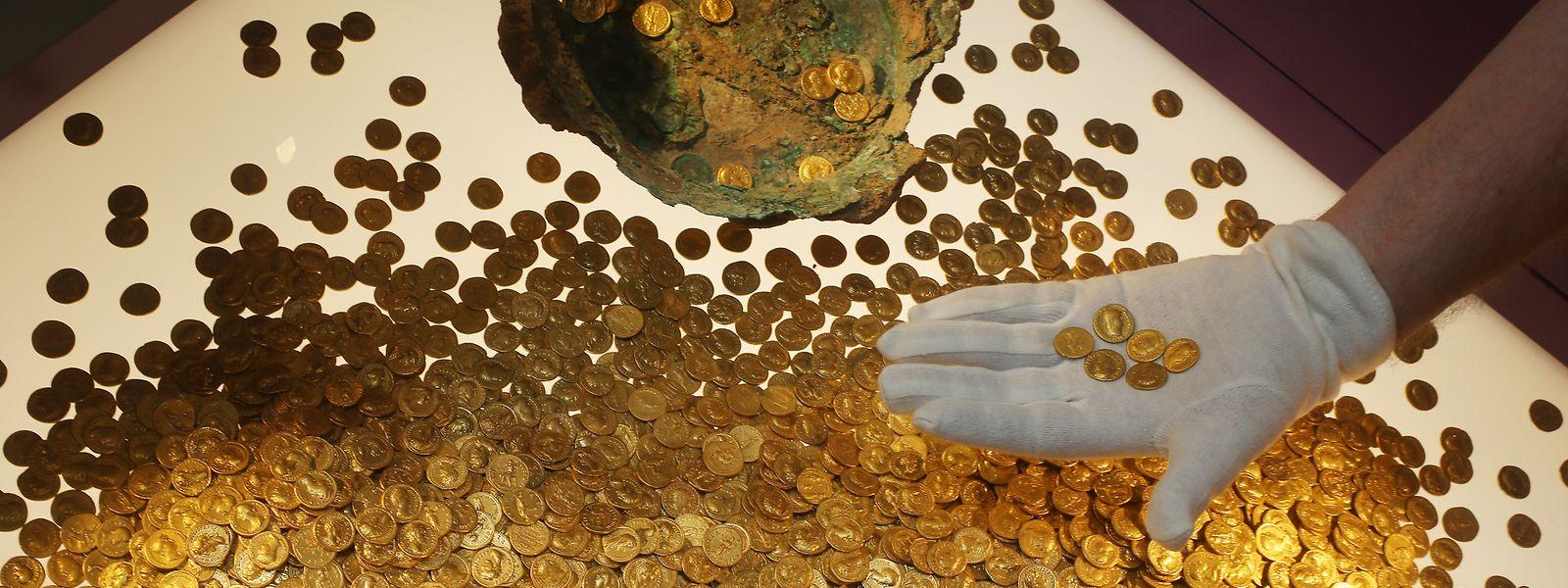 Der Numismatiker Karl-Josef Gilles platziert im Landesmuseum römische Goldmünzen in einer Vitrine. Es handelt sich um den weltweit größten Goldschatz der römischen Kaiserzeit: 18,5 Kilo schwer und rund 2.600 Münzen stark.