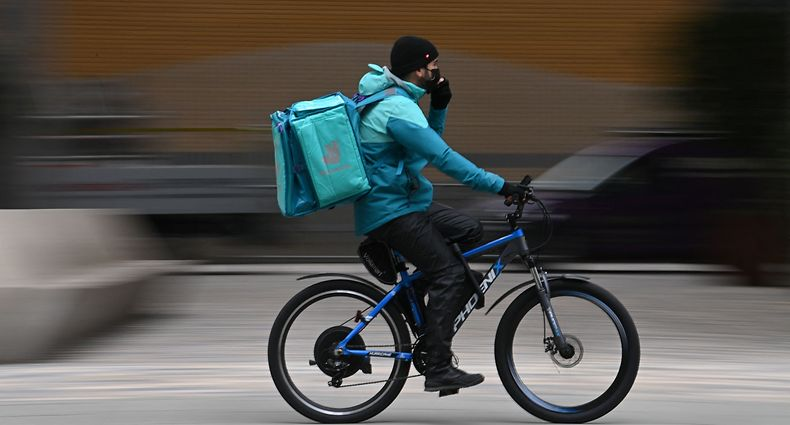 (FILES) In this file photo taken on March 26, 2021 a Deliveroo rider cycles through central London. - Britain's app-driven food delivery firm Deliveroo is set for London's largest stock market launch in a decade with a valuation of �7.6 billion, despite mounting criticism over its treatment of riders on March 30, 2021. (Photo by DANIEL LEAL-OLIVAS / AFP)