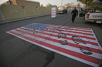TOPSHOT - A mock US flag is laid on the ground for cars to drive on in the Iraqi capital Baghdad on January 3, 2020, following news of the killing of Iranian Revolutionary Guards top commander Qasem Soleimani in a US strike on his convoy at Baghdad international airport. (Photo by AHMAD AL-RUBAYE / AFP)