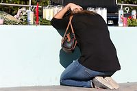 Fassunglos kniet eine trauernde Frau an der Gedenkstätte für die Opfer der Schießerei an der Marjory Stoneman Douglas High School in Florida.