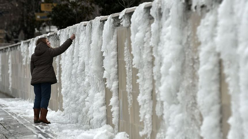 A girl touches a frozen wall in Thessaloniki, Greece. The icy conditions left many households in the Thessaloniki region without water as pipes froze or broke.