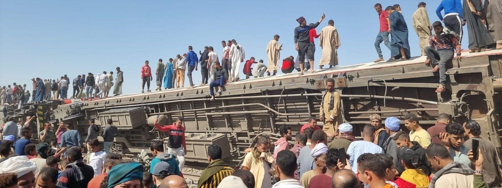 Männer springen nach dem Zusammenstoß zweier Züge von beschädigten Waggons, während Helfer und Rettungskräfte sich davor versammeln.