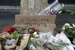 """A sign that reads, """"Never forget"""" is laced with flowers at the site of an attack in central east Paris"""