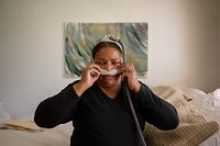 """Former 9/11 ground zero cleanup worker Rubiela Arias demonstrates the use of a Continuous Positive Airway Pressure (CPAP) device that she uses, following the diagnosis of breating dificulties associated with her work in the wake of the September 11, 2001 World Trade Center attacks, at her home in the Queens borough of New York on May 27, 2021. - Arias, who has been fighting for years for the legalization of the Hispanic workers who cleaned up """"the giant cemetery"""" at Ground Zero, has since suffered from various respiratory and stomach illnesses, as well as post-traumatic stress, among other mental ailments. For eight months after the attacks, tens of thousands of people -- many of them immigrants -- cleaned Ground Zero and nearby damaged buildings. They removed 1.8 million tons of rubble from the area and were paid between $7.50 and $10 an hour, just above the minimum wage at the time. They didn't know it then but the exposure to asbestos and other toxic materials exposed them to the risk of cancer, asbestosis and a host of respiratory illnesses, as well as post-traumatic stress, anxiety and depression. (Photo by Ed JONES / AFP)"""