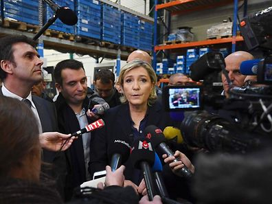 France's Front National (FN) far-right party's President and presidential candidate for the 2017 election Marine Le Pen (C), flanked by FN vice-president Florian Philippot (2-L), speak to journalists at the Fermap manufacturing factory in Forbach, eastern France, on January 18, 2017.  / AFP PHOTO / PATRICK HERTZOG