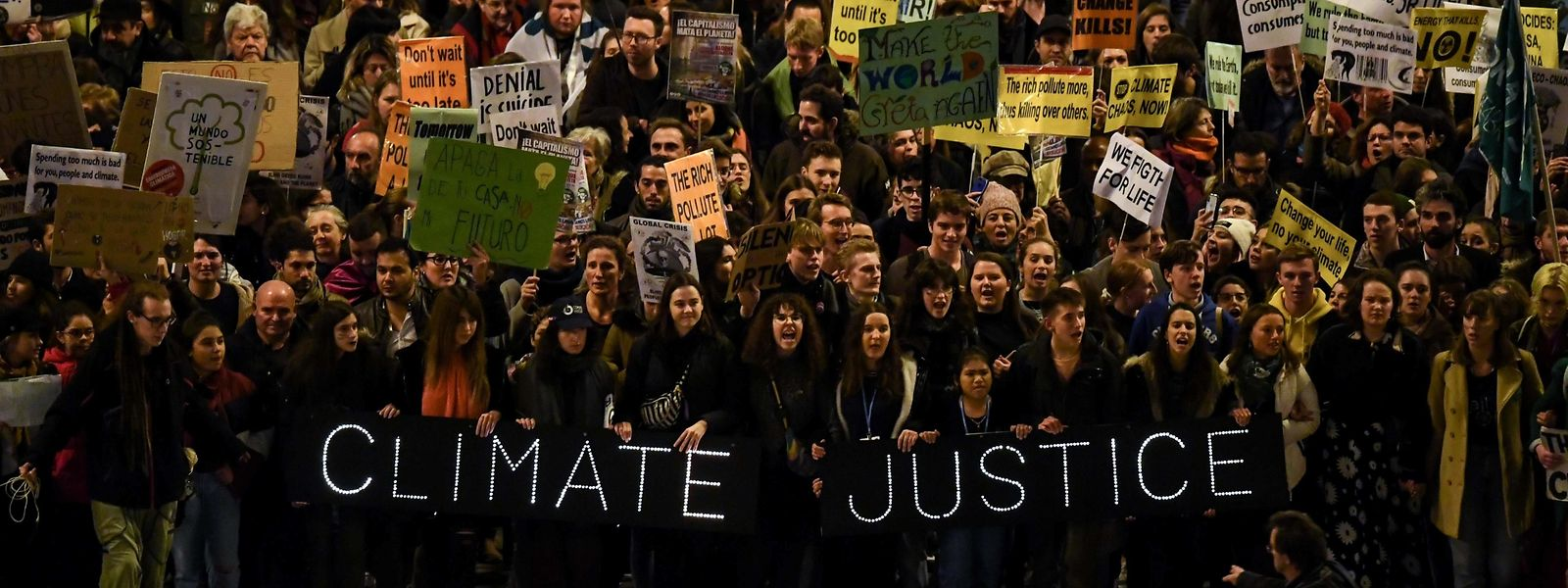 "Demonstrators hold a banner reading ""Climate Justice"" during a mass climate march to demand urgent action on the climate crisis from world leaders attending the COP25 summit, in Madrid, on December 6, 2019. - The main march takes place in Madrid on the sidelines of the UN climate conference, with a simultaneous rally in the Chilean capital, which had been due to host the 12-day gathering but was forced to pull out due to deadly anti-government protests. (Photo by GABRIEL BOUYS / AFP)"