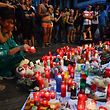 People stand next to flowers, candles and other items set up on the Las Ramblas boulevard in Barcelona as they pay tribute to the victims of the Barcelona attack, a day after a van ploughed into the crowd, killing 14 persons and injuring over 100 on August 18, 2017.  Drivers have ploughed on August 17, 2017 into pedestrians in two quick-succession, separate attacks in Barcelona and another popular Spanish seaside city, leaving 14 people dead and injuring more than 100 others. Some eight hours later in Cambrils, a city 120 kilometres south of Barcelona, an Audi A3 car rammed into pedestrians, injuring six civilians -- one of them critical -- and a police officer, authorities said. / AFP PHOTO / Pascal GUYOT