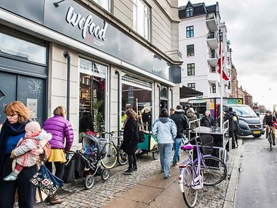 People walking past the Wefood supermarket that sells food past its sell-by date at Amager in Copenhagen, Denmark