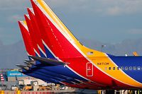 """(FILES) In this file photo taken on March 13, 2019 a group of Southwest Airlines Boeing 737 MAX 8 aircraft sit on the tarmac at Phoenix Sky Harbor International Airport in Phoenix, Arizona. The United States has followed countries around the world and has grounded all Boeing 737 Max 8 aircraft. - A Boeing 737 MAX aircraft operated by Southwest Airlines made an emergency landing on March 26, 2019, after experiencing an engine problem as it was being ferried from Florida to California, the US Federal Aviation Agency said. """"The aircraft returned and landed safely in Orlando,"""" the FAA said in a statement, adding that no passengers were on board the aircraft, which was being transferred to Victorville, California, for storage. (Photo by Ralph Freso / GETTY IMAGES NORTH AMERICA / AFP)"""