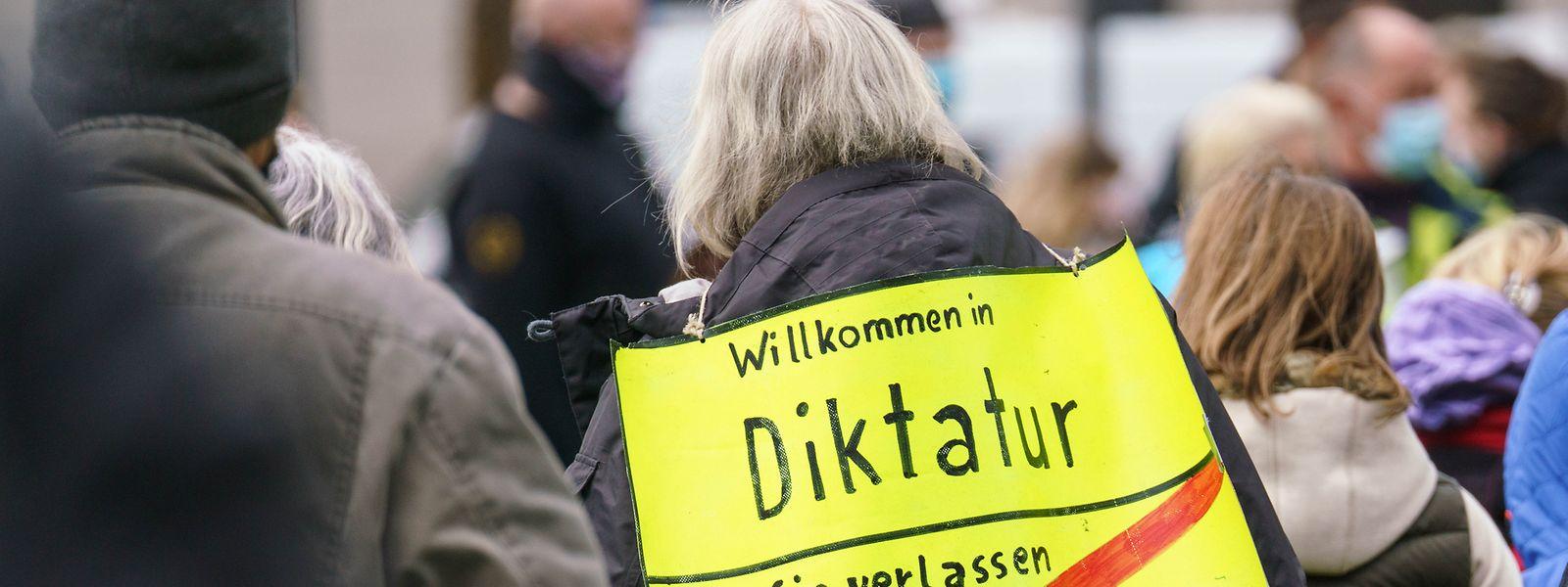 """Eine Demonstrantin steht bei einer Kundgebung der """"Querdenken""""-Bewegung mit einem Plakat mit der Aufschrift """"Willkommen in Diktatur - Sie verlassen Demokratie""""."""