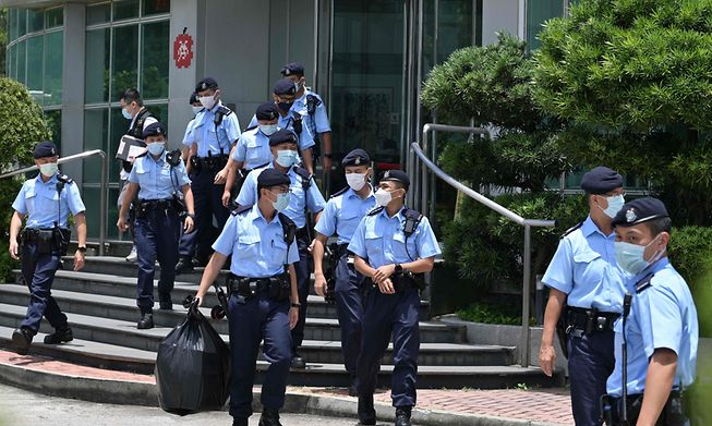 Police officers leave the Apple Daily newspaper offices in Hong Kong on June 17, 2021.