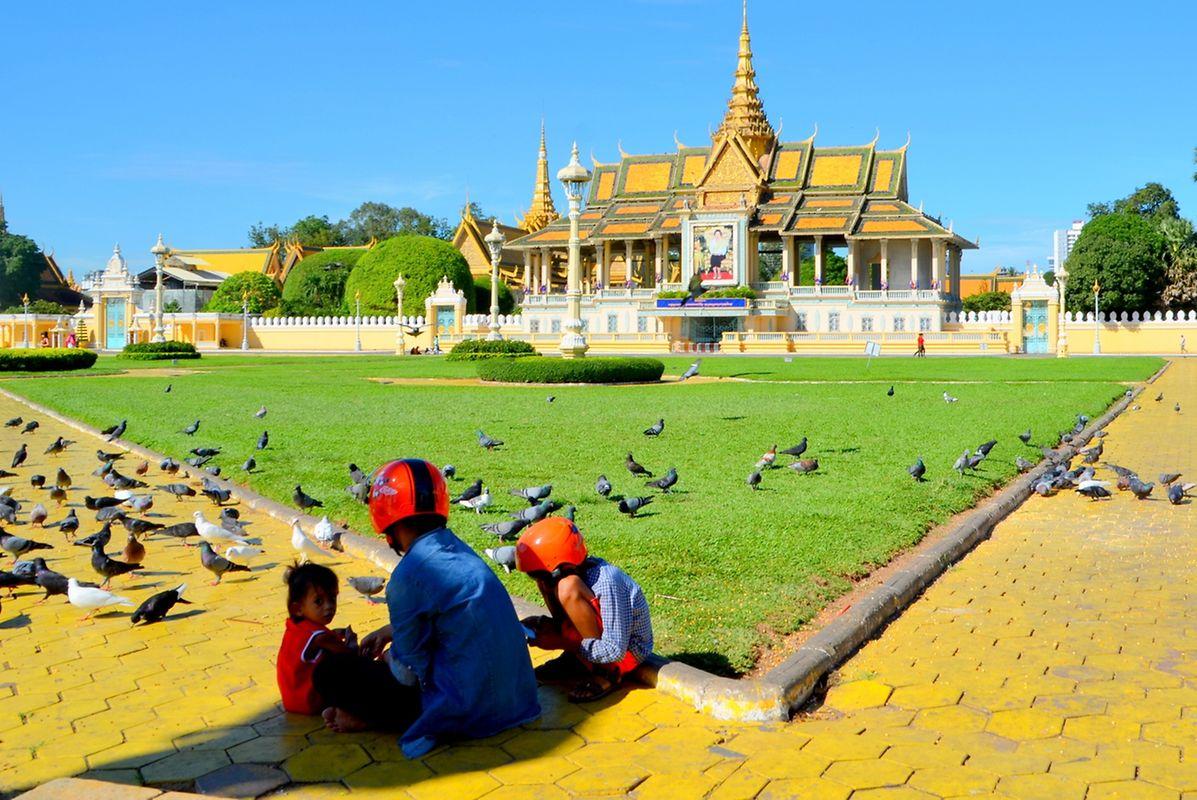 Une jeune mère et ses enfants prennent le petit déjeuner sur la place devant le palais