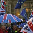 Anti-Brexit activists hold Union and EU-themed umbrellas and flags as they demonstrate with other protesters outside of the Houses of Parliament in central London on January 15, 2019. - Parliament is to finally vote today on whether to support or vote against the agreement struck between Prime Minister Theresa May's government and the European Union. (Photo by Daniel LEAL-OLIVAS / AFP)