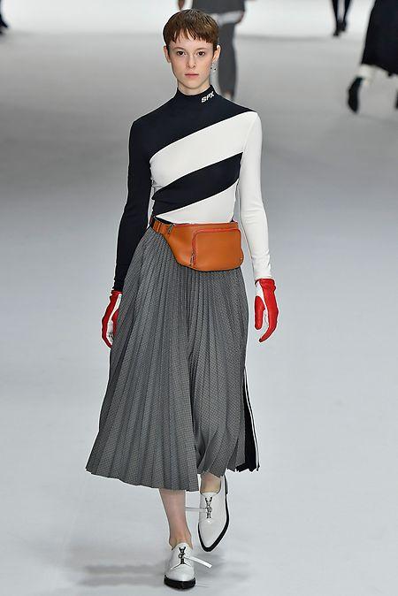 Sportmax verleiht dem klassischen Bundfaltenrock mit markanten Schürschuhen, Bauchtasche und engem Rollkragen-Pulli einen sportlichen Twist.