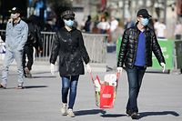 A couple wearing protective face masks carry their groceries on April 5 , 2020, in Brussels, as a strict lockdown is been in place for the past 3 weeks to stop the spread of COVID-19, the disease caused by the novel coronavirus. (Photo by Aris Oikonomou / AFP)