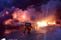 """This handout photograph released by Service Departemental d'incendie et des sec (SDIS) on September 27, 2019, shows firefighters at the scene of a blaze at a Lubrizol factory in Rouen, north-western France early September 26, 2019. - Firefighters have extinguished a huge blaze that broke out at a chemical factory in northern France and forced authorities to close schools and warn of pollution risks for the Seine river, local authorities said on September 27, 2019. The fire erupted early morning at a storage facility near the city of Rouen owned by Lubrizol, a manufacturer of industrial lubricants and fuel additives which is owned by the billionaire American investor Warren Buffett. (Photo by YACINE MOUFADDAL / SDIS / AFP) / RESTRICTED TO EDITORIAL USE - MANDATORY CREDIT """"AFP PHOTO / SDIS/YACINE MOUFADDAL"""" - NO MARKETING - NO ADVERTISING CAMPAIGNS - DISTRIBUTED AS A SERVICE TO CLIENTS"""
