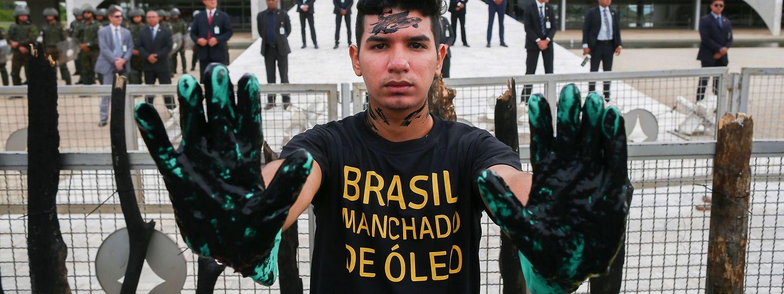"""Ein Greenpeace-Aktivist mit schwarz bemalten Handschuhen und der T-Shirt-Aufschrift """"ölverschmutztes Brasilien"""" protestiert vor dem Amtssitz von Jair Bolsonaro."""