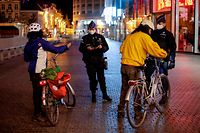 Police officers wearing protective face masks control people riding bikes as they patrol at the start of the curfew in Brussels on October 19, 2020 as a measure against the spread of the COVID-19 pandemic caused by the novel coronavirus. - The consultative committee introduced stricter measures to reduce the risk of spreading COVID-19 as the contamination numbers are spiking. A curfew will be installed in the entire country from October 19, and no one will be allowed to leave their home between midnight and 5pm. (Photo by THIERRY ROGE / Belga / AFP) / Belgium OUT